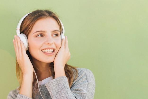 音楽を聴く彼女の頭の上にヘッドフォンを持つ若い女