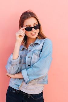 桃の背景に対して立っている眼鏡を通して覗く魅力的な若い女性