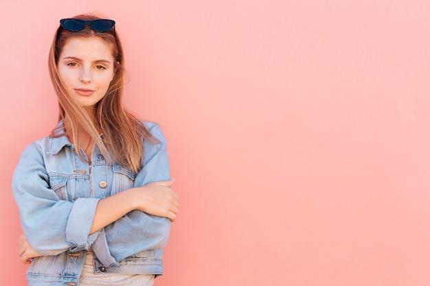 桃の背景に対して立っている魅力的な若い女性