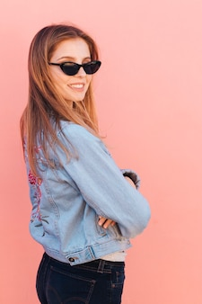 ピンクの背景に対して肩越しに見ているサングラスをかけているファッショナブルな若い女性