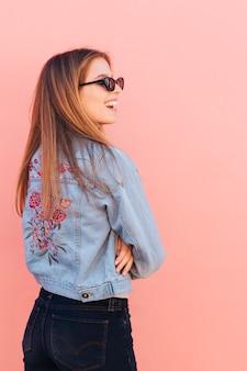 彼女の腕を持つ青いジャケットの若い女性はピンクの背景に対して立っているを渡った