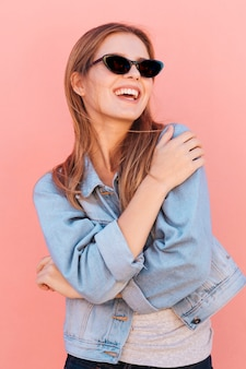 ピンクの背景に対して幸せな金髪の若い女性の肖像画