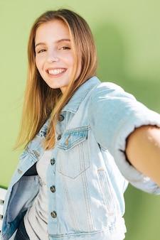 緑の背景に対して金髪の若い女性の肖像画を笑顔