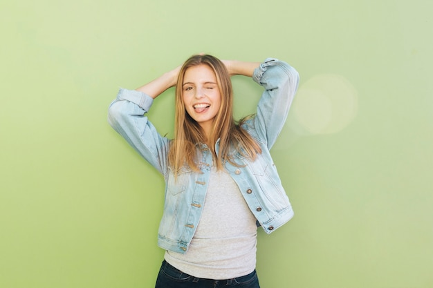 Улыбается молодая женщина с ее руки за головой, подмигивая на зеленом фоне