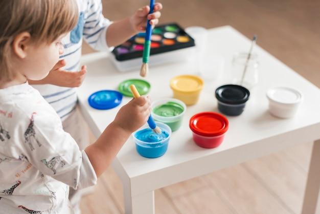 家で一緒に絵を描く子供たち