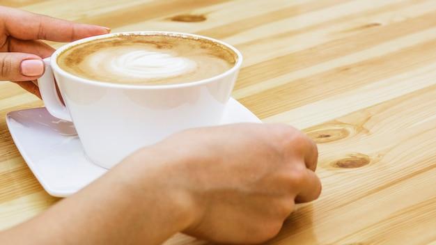 一杯のコーヒーを取って手