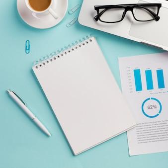 コーヒーカップ、眼鏡、ノートパソコン、眼鏡、データ用紙、ペンと空白のスパイラルメモ帳