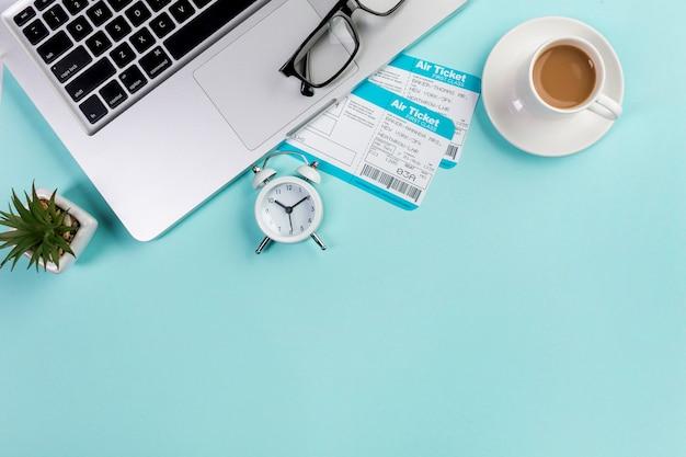 Поднятый вид двух авиабилетов с кофейной чашкой, ноутбуком, очками, будильником на синем офисном столе