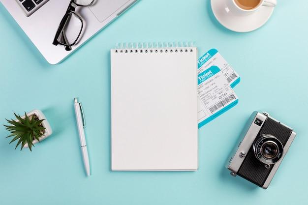 ノートパソコン、眼鏡、ペン、カメラ、青い机の上のコーヒーカップに囲まれた航空券で空白のスパイラルメモ帳
