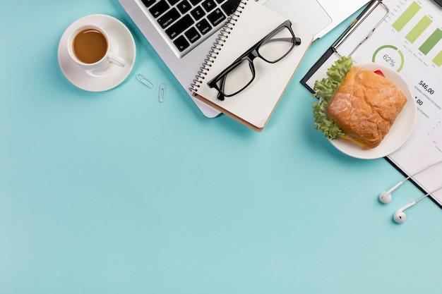 スパイラルメモ帳、ラップトップ、眼鏡、青い机の上のイヤホンでの朝食します。