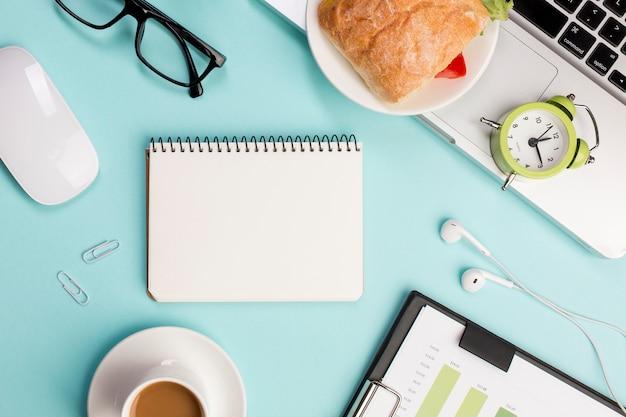 青い背景に文房具、ノートパソコン、マウス、目覚まし時計付き事務机の俯瞰
