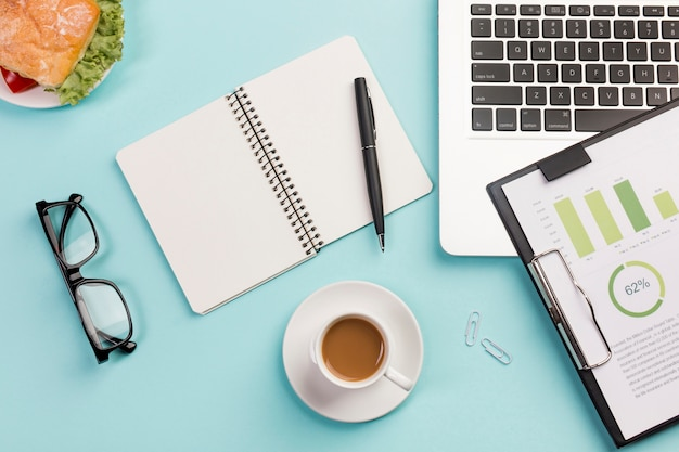 Бутерброд, чашка кофе, очки, спиральный блокнот, ручка, ноутбук и буфер обмена с планом бюджета на синем столе