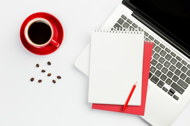 コーヒーカップ、白い背景に対して開いているラップトップ上のスパイラルメモ帳とコーヒー豆