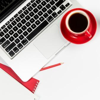 白い背景の上の開いているラップトップ上の赤いコーヒーカップ
