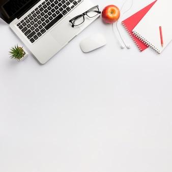 ノートパソコン、眼鏡、マウス、イヤホン、白い背景の上のスパイラルメモ帳とアップルのサボテンの植物
