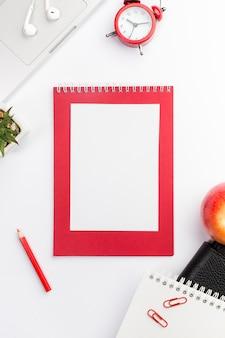 空白のスパイラルメモ帳、目覚まし時計、ラップトップ、アップル、白い背景の上のスパイラルメモ帳
