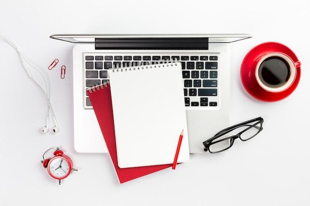 事務用品、ラップトップ、コーヒーカップ、目覚まし時計、白い机の上の眼鏡のオーバーヘッドビュー