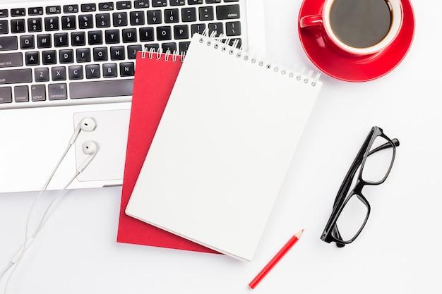 イヤホンとコーヒーカップと眼鏡のラップトップ上のスパイラルメモ帳