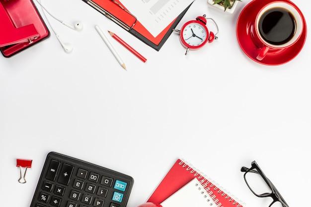 赤い文房具、目覚まし時計、そして白い机の上の電卓