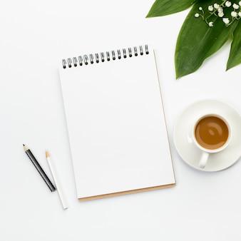 Черно-белые цветные карандаши, пустой спиральный блокнот, чашка кофе и листья на офисном столе