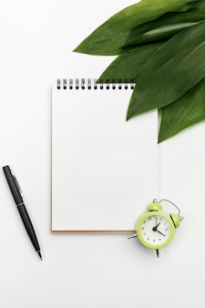 目覚まし時計と白い背景の上のペンとスパイラルメモ帳に緑の葉