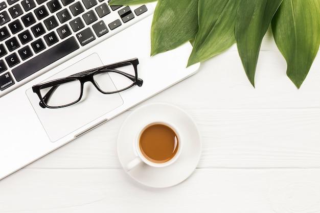 黒い眼鏡と木製の机の上のコーヒーカップと開いているラップトップ上の葉