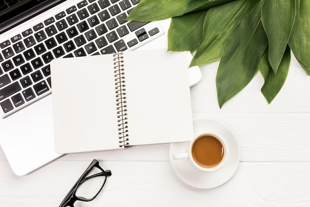 スパイラルメモ帳と眼鏡と木製のオフィスの机の上のコーヒーカップとラップトップ上の葉