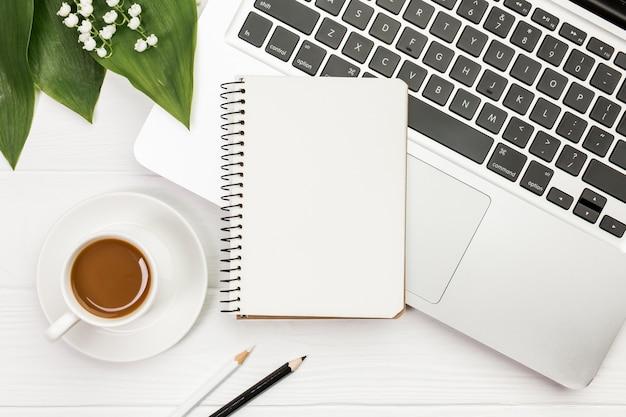 木製の机の上の色鉛筆でラップトップ上のスパイラルメモ帳とコーヒーカップ