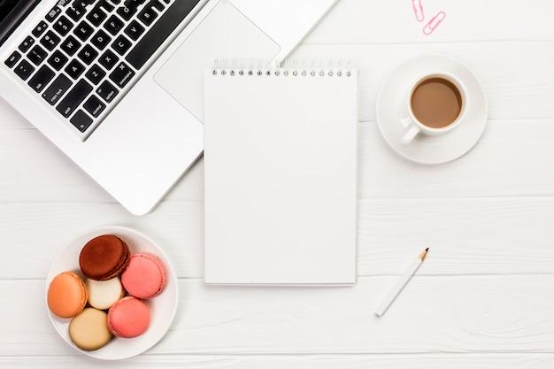 カラフルなマカロンと木製の事務机の上のラップトップ上のスパイラルメモ帳とコーヒーカップ