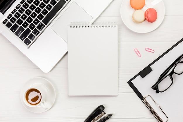 ノートパソコン、マカロン、クリップボードと白いオフィスの机の上の眼鏡とコーヒーカップのスパイラルメモ帳