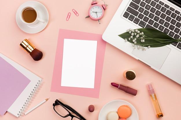 化粧品、マカロン、目覚まし時計、コーヒーカップ、色付きの背景上のラップトップを持つ空白のカード