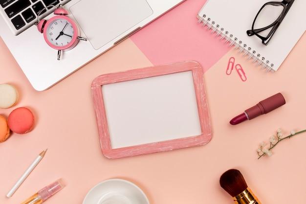 色付きの背景に化粧ブラシ、マカロン、ホワイトボードのスレートとラップトップ上の目覚まし時計
