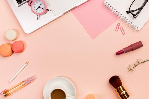 マカロン、コーヒーカップ、化粧筆、目覚まし時計、ピーチ色の背景上のラップトップ