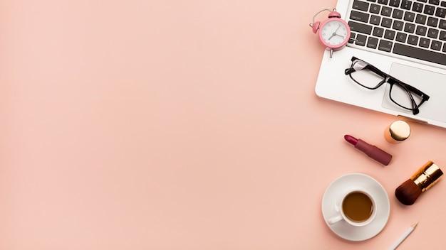目覚まし時計、コーヒーカップと桃の背景に化粧品が付いているラップトップ上の眼鏡