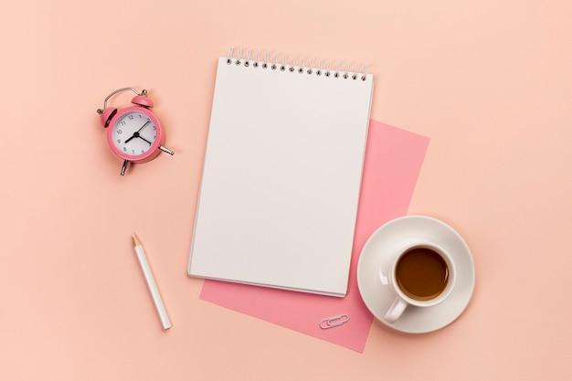桃の色の背景に目覚まし時計、鉛筆、スパイラルメモ帳、紙、コーヒーカップ