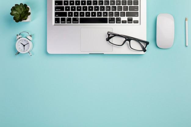 サボテンの植物、目覚まし時計、ノートパソコン、眼鏡、マウス、青い机の上の鉛筆