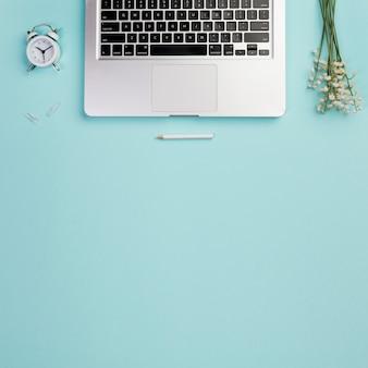 目覚まし時計、ノートパソコンと青いオフィスの机の上の谷のユリと鉛筆の俯瞰