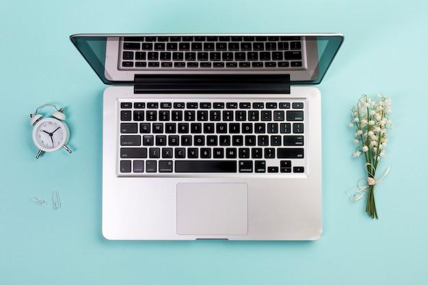 目覚まし時計、ペーパークリップ、青いビジネスデスクで開いているノートパソコンと谷のユリの花束
