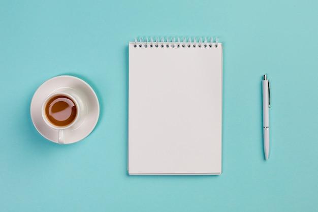 コーヒーカップ、空白のスパイラルメモ帳と青いオフィスの机の上のペン