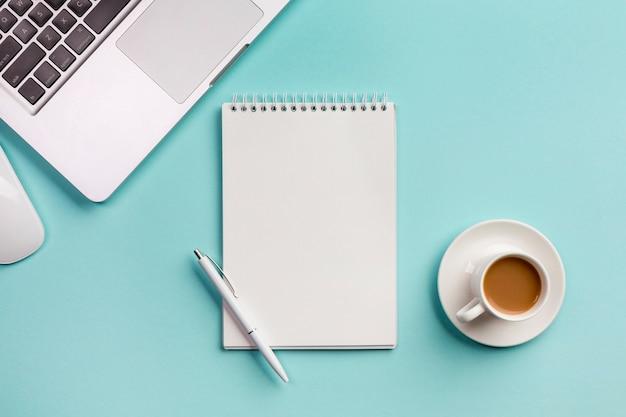 スパイラルメモ帳、マウス、コーヒーカップ、青い事務机の上のペンを持つノートパソコン
