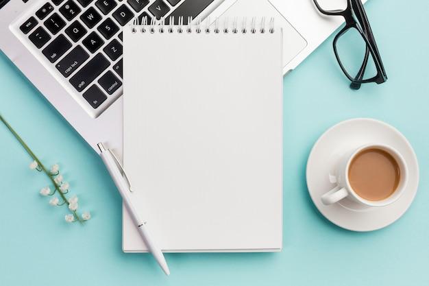 Ручка и спиральный блокнот на ноутбуке с очками, цветочной веточкой и кофейной чашкой на синем офисном столе