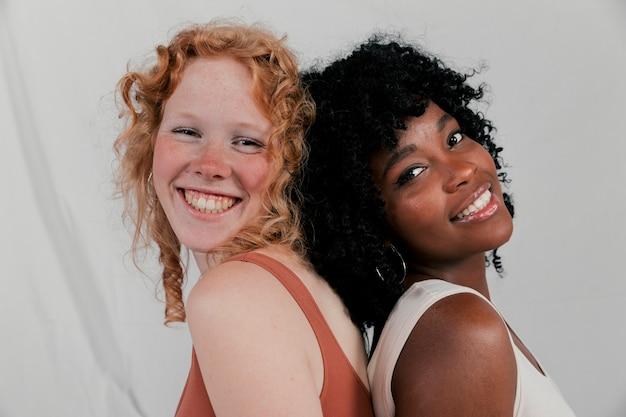 カメラを見て背中合わせに傾いている若い多民族女性の友人の笑顔