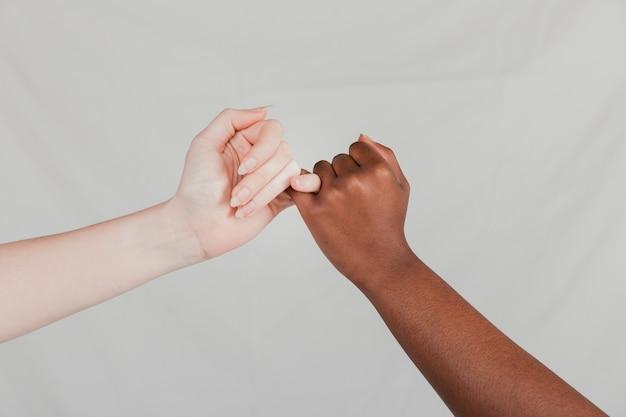 灰色の背景に対して小指の約束を作る公正で暗い女性の手のクローズアップ