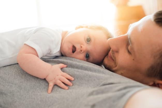 父の上に横たわるかわいい赤ちゃん