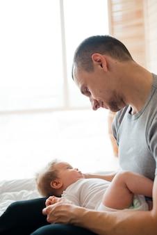 父は膝の上に赤ちゃんを抱える