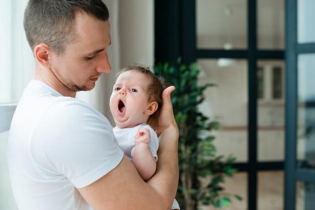 あくびをする赤ちゃんを抱いて父
