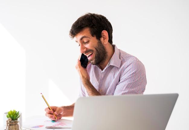 携帯電話とラップトップで働くビジネスマン