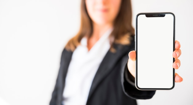 空白の画面を持つ携帯電話を示す手