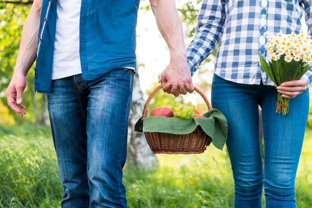 牧草地にピクニックバスケットを持って愛好家
