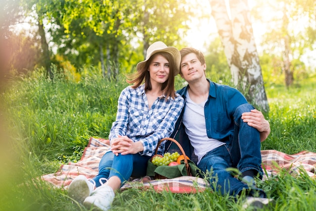 空き地に素敵なピクニックを持っているカップル